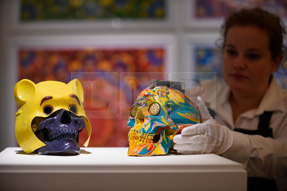 """© Licensed to London News Pictures. 14/09/2018. LONDON, UK. A technician inspects (L to R) """"Winnie The Pooh"""", 2005, by Gary Hume (Est. GBP400-600) and """"The Hours Spin Skull"""", 2009, by Damien Hirst (Est. GBP3,000-4,000) at a preview of the """"Yellow Ball: The Frank and Lorna Dunphy Collection"""" sale at Sotheby's in New Bond Street.  Frank Dunphy was Damien Hirst's former business manager and mentor.  Over 200 works will be auctioned by Sotheby's on 20 September 2018.  Photo credit: Stephen Chung/LNP"""