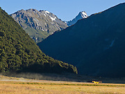 A small yellow Skywagon airplane takes off from Siberia Valley airstrip in Mount Aspiring National Park in the Southern Alps, South Island, New Zealand. In 1990, UNESCO honored Te Wahipounamu - South West New Zealand as a World Heritage Area.