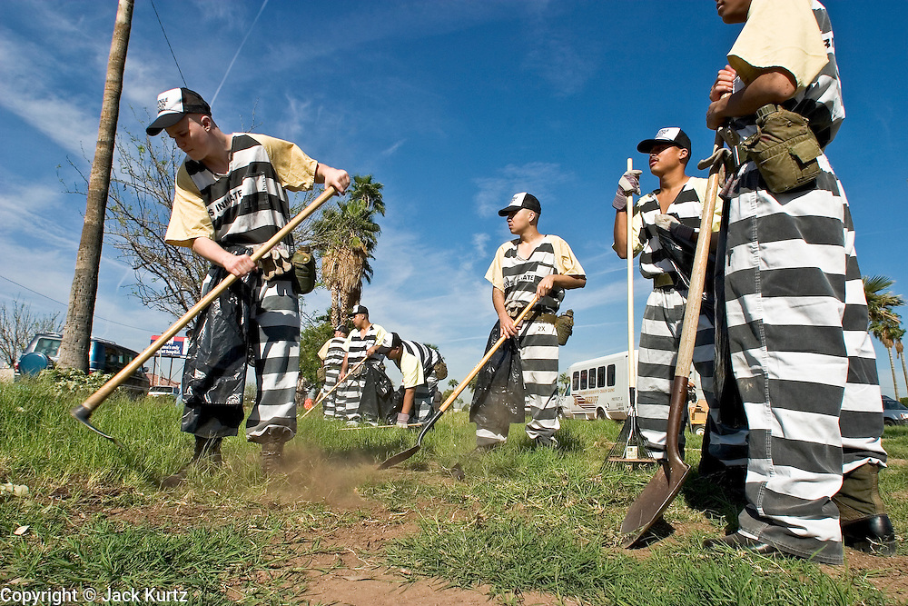 """24 MARCH 2004 - PHOENIX, AZ, USA: Members of the Maricopa County Jail's Juvenile Chain Gang clean up a vacant lot a worksite in Phoenix, AZ, March 24, 2004. The juveniles volunteer to serve Maricpoa County Sheriff Joe Arpaio's chain gang. The sheriff, who claims to be """"the toughest sheriff in America,"""" has chain gangs in both the men's and women's jails and now has a chain gang for juveniles sentenced and serving time as adults in the county jail system. The sheriff claims it is the only juvenile chain gang in the country.   PHOTO BY JACK KURTZ"""