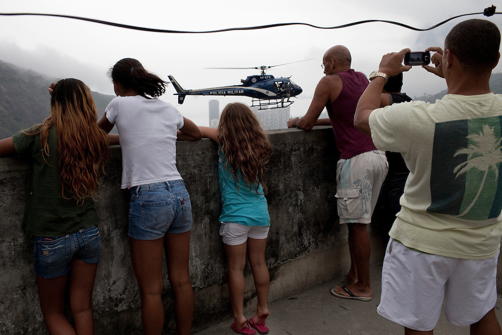 Residents watch as a police helicopter overflies nearby during an incursion by security forces into 'Rocinha', one of Brazil's biggest slums controlled by drug traffickers, on November 13, 2011, Rio de Janeiro, Brazil. Photo by Mauricio Lima for The New York Times