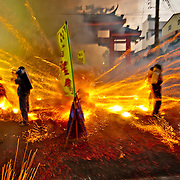 A barrage of firecrackers and bottle rockets blast gods in palanquins and their bearers at the annual Yenshui beehive fireworks festival in Yanshui Village, Tainan County, Taiwan