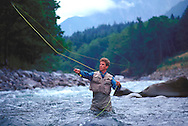 Lifestyle image of fly fisherman casting line on the Skykomish River in Washington State.