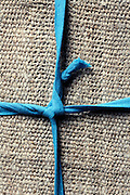 blue string knot on a rough canvas background