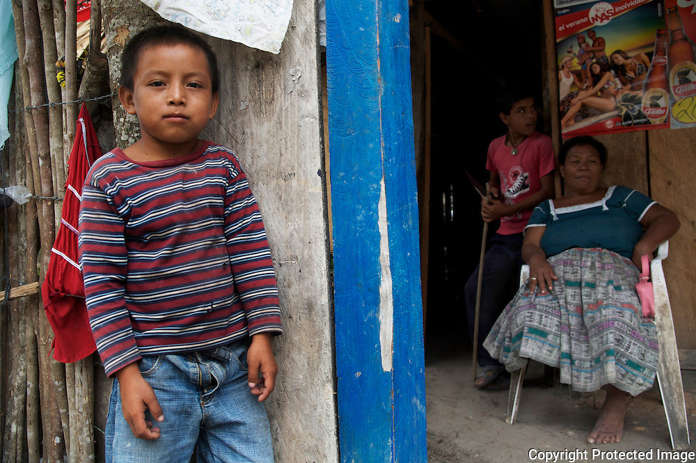 Mayan boy in front of family store with his grandmother and cousin in San Pedro, Guatemala
