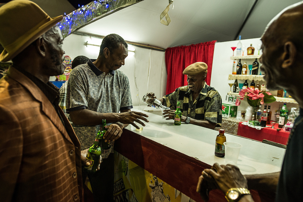"""PORT OF SPAIN, TRINIDAD - FEBRUARY 15, 2017: Men share jokes and beers while partying (called """"liming"""") in Queen's Park Savannah.  PHOTO: Meridith Kohut for The New York Times"""