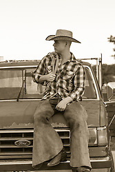 young cowboy sitting on top of an old truck outdoors