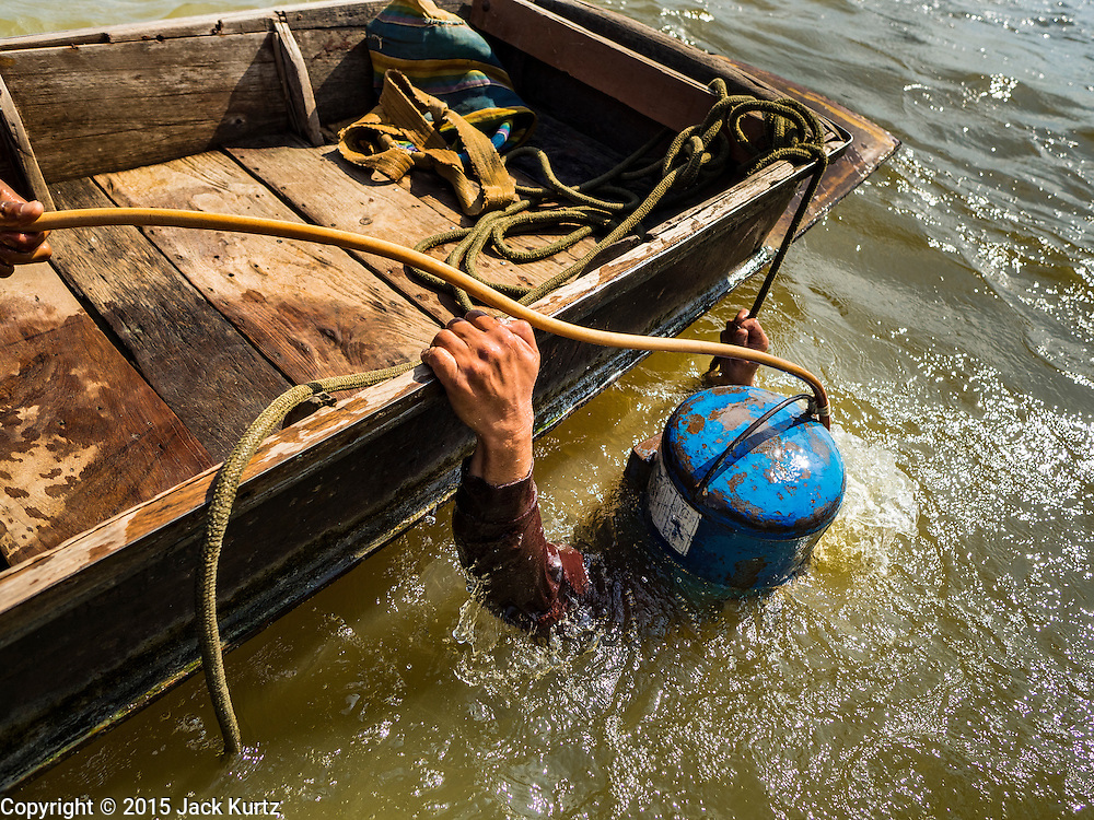 14 OCTOBER 2015 - BANGKOK, THAILAND:  A diver surfaces from the bottom of the Chao Phraya River in Bangkok. Divers work in two man teams on small boats in the Chao Phraya River. One person stays in the boat while the diver scours the river bottom for anything that can be salvaged and resold. The divers usually work close to shore because the center of the river is a busy commercial waterway with passenger boats and commercial freight barges passing up and down the river all day long. The Chao Phraya is a dangerous river to dive in. It's deep, has large tidal fluctuations, is fast flowing and badly polluted. The divers make money only when they sell something.   PHOTO BY JACK KURTZ