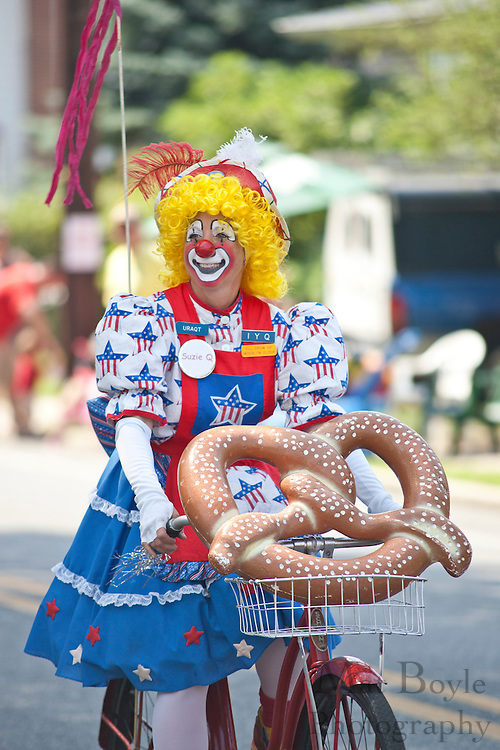 A member of the Cunard Clown group rides a bike at the 2010 Pitman NJ 4th of July Parade.
