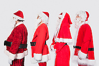 People in Santa costume standing in row against gray background