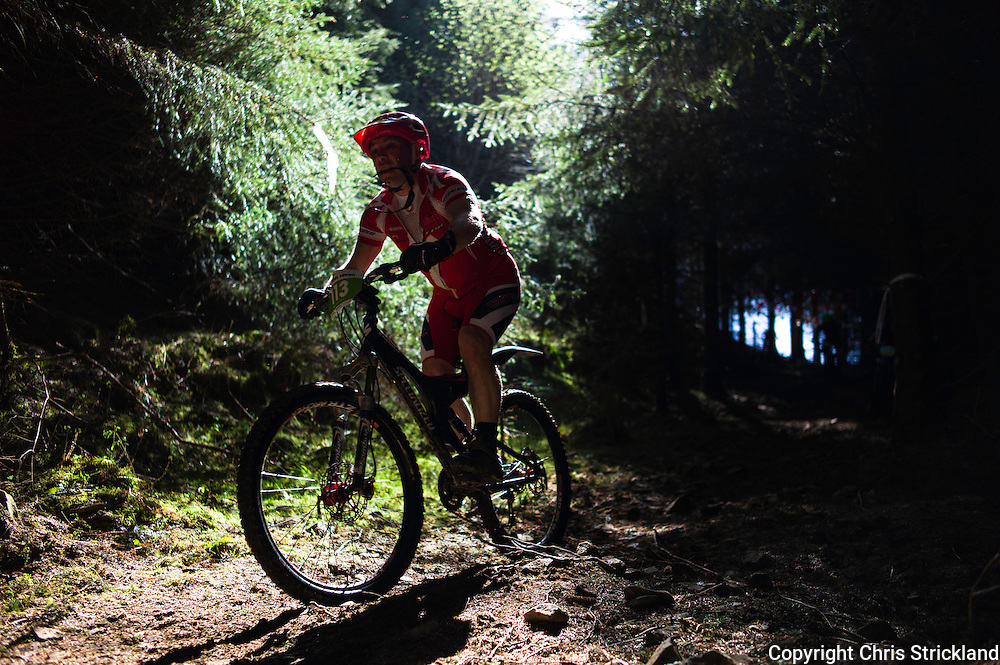 Glentress, Peebles, Scottish Borders, UK. 23rd May 2015. A mountain biker carries his sunglasses in his mouth while navigating through thick forestry in the Glentress 7 race during Tweedlove Festival. The aim is to complete as many laps of an 11km course during the 7 hour time limit.