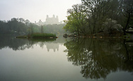 A misty scene with the Beresford apartment building at the Lake in Central Park, New York City.