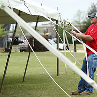 Adam Robison | BUY AT PHOTOS.DJOURNAL.COM<br /> Brian Manning, co-owner of Tupelo Tent Company, sets the tension on a 40x40 tent that is being installed for this weekends Color Vibe 5K and NOleput Festival Thursday morning at Fairpark in Tupelo.