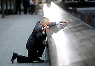 Robert Peraza, who lost his son Robert David Peraza in the September 11, 2001 terrorist attacks, kneels in front of his son's name at the North Pool of the 9/11 Memorial during tenth anniversary ceremonies at the site of the World Trade Center on 11 September 2011, in New York, New York, USA.