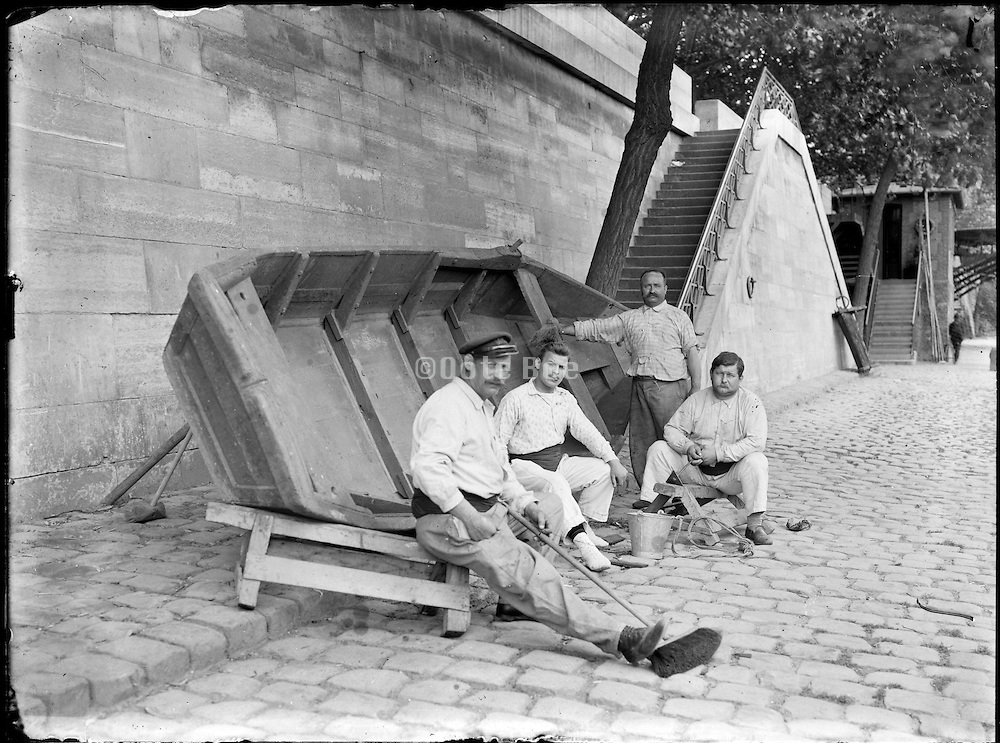 small boat and working men sitting along the river Seine Paris around 1900