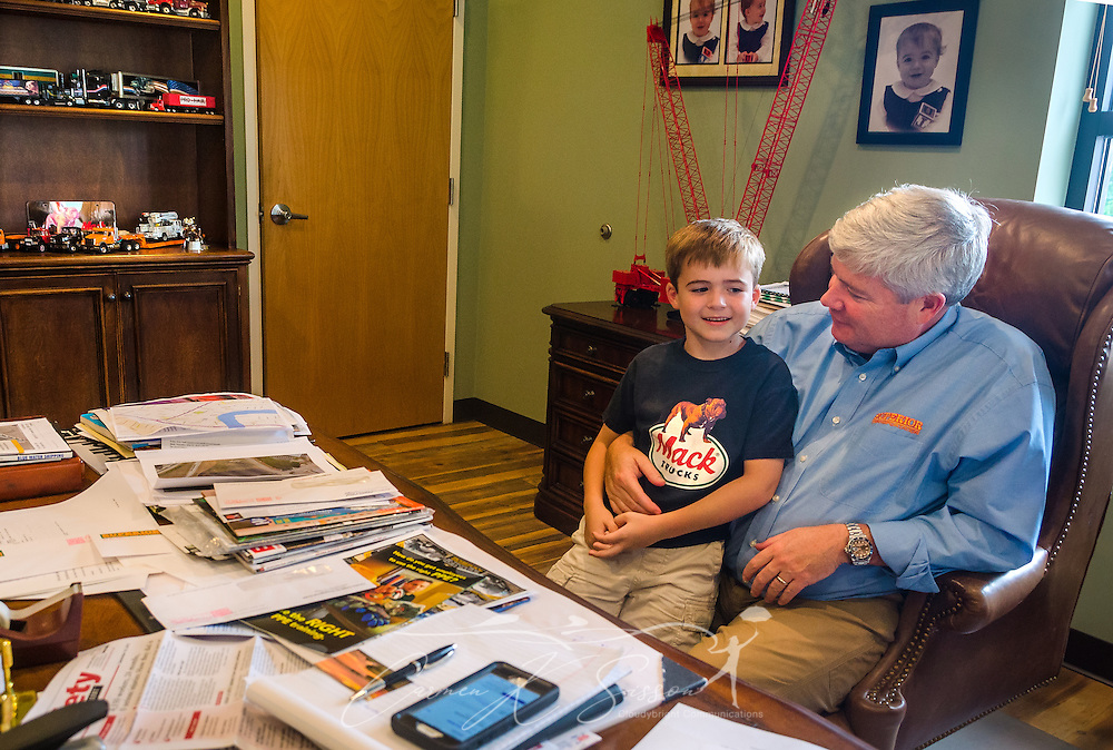 "Six-year-old James Barber greets his father, Pat Barber, as he drops by Superior Transportation to visit and ""work with dad,"" Sept. 30, 2015, in North Charleston, South Carolina. Barber started the company in 1998. James, 6, is already showing a big interest in the company and its Mack trucks, and Barber says he hopes he will follow in his footsteps and carry on the family legacy.  (Photo by Carmen K. Sisson/Cloudybright)"