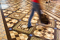 The blur of a passer by on the floor of the Saigon Central Post Office.
