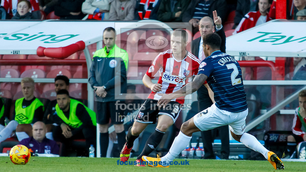 Jake Bidwell of Brentford and Cyrus Christie of Derby County with Brentford Manager Mark Warburton in the background during the Sky Bet Championship match between Brentford and Derby County at Griffin Park, London<br /> Picture by Mark D Fuller/Focus Images Ltd +44 7774 216216<br /> 01/11/2014