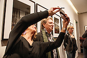 Andy Summers, former guitar player of the Police, writer and photographer, poses while a fan takes a selfie with him at Leica Gallery where there is an exhibition of his photographs in Milan, March 22, 2016. &copy; Carlo Cerchioli<br />