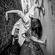 Model Anna Pauline crawls up a wall like a spider.