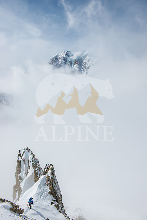 Squash Falconer, a female British adventurer as seen druing traverse of a rock feature on Aiguilles Marbrées. In the background the iconic south face of Mont Blanc.