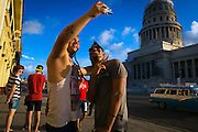 Marlon Marrero, left, and Rolando Labarrare take a selfie near the National Capitol Building in Old Havana. (David Albers/Staff)