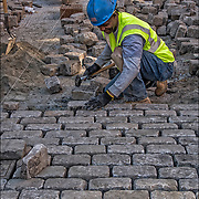 African American blue collar worker repairing and replace cobblestones on city street after underground repairs.<br /> <br /> Cobblestone is a natural building material based on cobble-sized stones, and is used for pavement roads, streets, and buildings. Cobblestones were largely replaced by quarried granite setts.  Setts were relatively even and roughly rectangular stones that were laid in regular patterns. <br /> <br /> There are not many of the older such streets left because theyhave been paved over with asphalt.