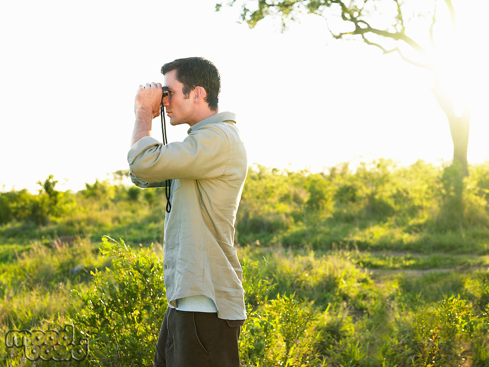 Mid adult man standing in fields looking through binoculars side view