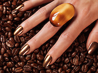 Closeup of woman's hands with brown nail polish and a ring on coffee beans