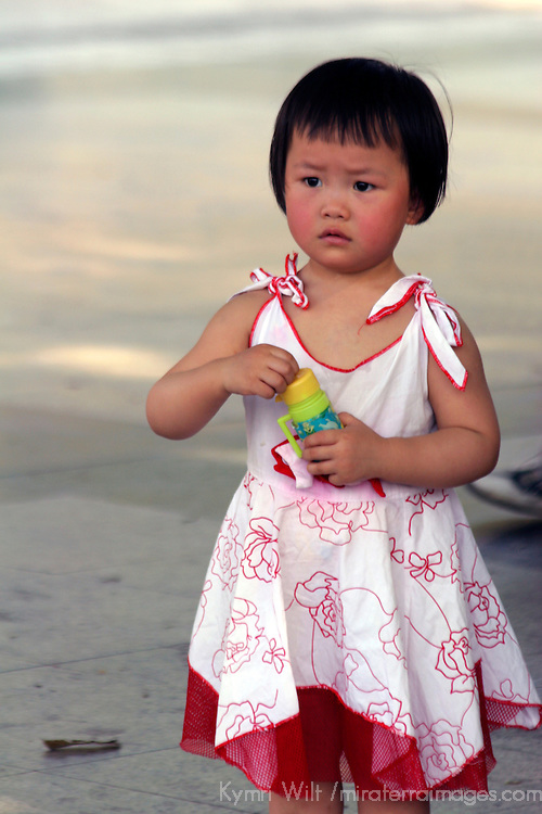 Asia, China, Chongqing. Young girl blowing bubbles at the park.