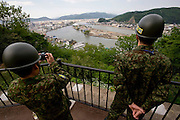 Self Defense Forces personnel take photos of the damage caused by the March 11 tsunamis from a hill in Ishinomaki City, Miyagi Prefecture, Japan on 25 May, 2011..Photographer: Robert Gilhooly