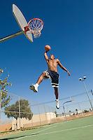 Basketball player mid-air dunking ball