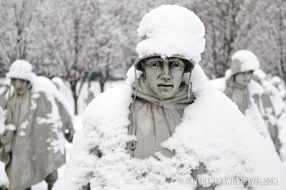 "A statue of a soldier at the Korean War Veterans Memorial on the National Mall on a snowy winter morning. The Korean War Veterans Memorial, unveiled in 1992, sits on the northwestern end of the National Mall, not far from the Lincoln Memorial. It consists of several elements designed by different people and groups. It has a triangular footprint with the main elements being ""The Column"" consisting of 19 stainless steel solders, each over 7 feet tall, and a reflective granite wall etched with the faces of thousands of Americans who lost their lives in the war. At one end of the triangle, behind the soldiers, is a grove of trees. At the other is a large American flag and a small Pool of Remembrance. Among the designers were Frank Gaylord (the soldiers) and Louis Nelson (the reflecting granite wall)."