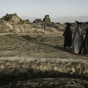 A trio of Afghanistan women walk near a brickmaking factor just outside Kabul, Afghanistan.