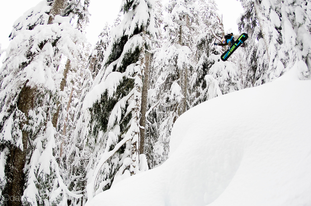 Professional snowboarder Sammy Luebke, soars through a snowy forest near Mt. Baker, Washington, USA.