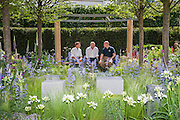 Actor Ross Kemp with the designer and Rory Mckenzie a wounded veteran (blue shirt) on the Hope on the Horizon garden.  The<br /> &lsquo;Hope on the Horizon&rsquo; garden in aid of Help for Heroes: produced by building and landscaping firm Farr and Roberts&rsquo;, making their debut; designed by Matthew Keightley (29), as a result of his brother Michael&rsquo;s involvement with the armed forces, having served on four tours to Afghanistan and due for his fifth this year; and sponsored by the David Brownlow charitable foundation. The garden layout is based on the shape of the Military Cross, the medal awarded for extreme bravery. Granite blocks will represent the soldiers&rsquo; physical wellbeing and the planting represents their psychological wellbeing at various stages of their rehabilitation. Both evolve through the garden from a rough, unfinished, over-grown beginning through to a perfectly sawn, structured end. An avenue of hornbeams draws the attention through the entire garden to a sculpture resembling a hopeful horizon; a reminder to the soldiers that they all have a bright future ahead. As well as areas to recline and reflect, the garden offers focal points all the way through. Cool, calming colours are used throughout, helping to emphasise the fact that it will be a serene, contemplative space. After the Show, the garden will be moved and set within the grounds at Help for Heroes Recovery Centre at Chavasse VC House in Colchester, Essex. The garden will offer a serene, peaceful haven to contemplate and inspire a bright future and to support the challenging journey to recovery. The Chelsea Flower Show 2014. The Royal Hospital, Chelsea, London, UK.  19 May 2014.