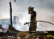 A firefighter wipes away sweat while fighting a fire that destroyed a Hays County home on Tues., Sept. 27, 2011.  <br /> Ashley Landis FOR AMERICAN STATESMAN