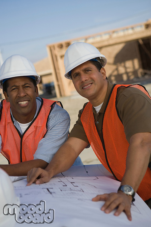 Two architects looking at blueprints