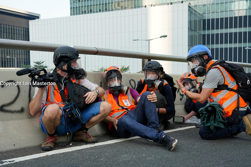 Hong Kong. 1 October 2019. After a peaceful march through Hong Kong Island by an estimated 100,000 pro democracy supporters, violent flared up at Tamar, Admiralty and moved through Wanchai district. Police used teargas and baton rounds and water cannon. Hard core group lit fires, threw bricks and Molotov cocktails at police. Violence continues into evening. SKY news crew sheltering from police baton rounds. Iain Masterton/Alamy Live News.