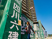 "15 FEBRUARY 2019 - SIHANOUKVILLE, CAMBODIA:  A Cambodian woman goes into the Blue Bay casino and resort construction site in Sihanoukville. There are about 80 Chinese casinos and resort hotels open in Sihanoukville and dozens more under construction. The casinos are changing the city, once a sleepy port on Southeast Asia's ""backpacker trail"" into a booming city. The change is coming with a cost though. Many Cambodian residents of Sihanoukville  have lost their homes to make way for the casinos and the jobs are going to Chinese workers, brought in to build casinos and work in the casinos.      PHOTO BY JACK KURTZ"