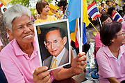 05 MAY 2010 - BANGKOK, THAILAND: A woman holds up a photo of Thai King Bhumibol Adulyade while she waits for his motorcade, Wednesday, May 5. People on the street in front of the Grand Palace in Bangkok wait for Thai King Bhumibol Adulyade, Wednesday, May 5. Wednesday was Coronation Day in Thailand, marking the 60th anniversary of the coronation of Thai King Bhumibol Adulyade, also known as Rama IX. He is the world's longest serving current head of state and the longest reigning monarch in Thai history. He has reigned since June 9, 1946 and his coronation was on May 5, 1950, after he finished his studies. The King is revered by the Thai people. Thousands lined the streets around the Grand Palace hoping to catch a glimpse of the King as his motorcade pulled into the palace. The King has been hospitalized since September 2009, making only infrequent trips out of the hospital for official functions, like today's ceremonies.   PHOTO BY JACK KURTZ