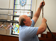 13 MAY 2012 -- FESTUS, Mo. -- Craig Brooks reaches high to ring the church bell one last time to call believers to worship at  the First Presbyterian Church in Festus Sunday, May 13, 2012. The congregation, which is merging with nearby Grace Presbyterian Church in neighboring Crystal City, held its final service Sunday. Photo © copyright 2012 Sid Hastings.