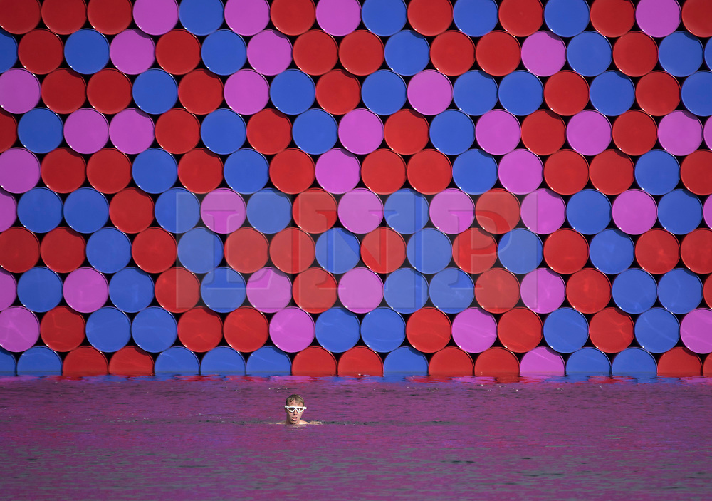 © Licensed to London News Pictures. 18/06/2018. London, UK. A swimmer passes Christo's latest work 'The Mastaba' on The Serpentine in Hyde Park. The 20m high installation, made up of 7,506 horizontally stacked barrels, is 30m wide and 40m long. Photo credit: Peter Macdiarmid/LNP