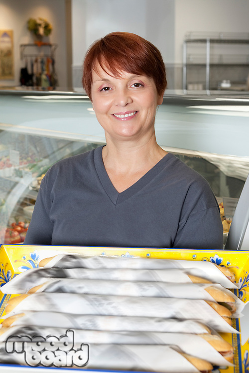 Portrait of woman with tray of wrapped baguettes