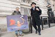 Downing Street, London, UK. 3rd December, 2014. Political Artist, Kaya Mar, displays his new painting of George Osborne as ministers leave Downing Street on the day the Chancellor is due to deliver his Autumn Statement in the House of Commons. Pictured:  Vince Cable.