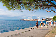 Tourists going for a walk at coast or beach of. Piran. Slovenia. Eastern Europe.