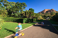 Children cycle in Queens Gardens under the watchful eye of Castle Hill which dominates the Townsville skyline.