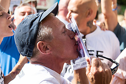 A Tommy Robinson supporter kisses his picture on a placard as he celebrates Robinson's release on Bail as counter protesters demonstrate outside The Royal Courts of Justice in London as an appeal by lawyers representing right wing activist Tommy Robinson secure a new hearing to be held at The Old Bailey, following his imprisonment on contempt of court charges. London, August 01 2018.