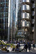 Londoners enjoy a warm eafternoon beneath the tall architecure of the Lloyds Building (right) and other financial services offices in the City of London, the capital's historic financial district, on 2nd August 2018, in London, England.