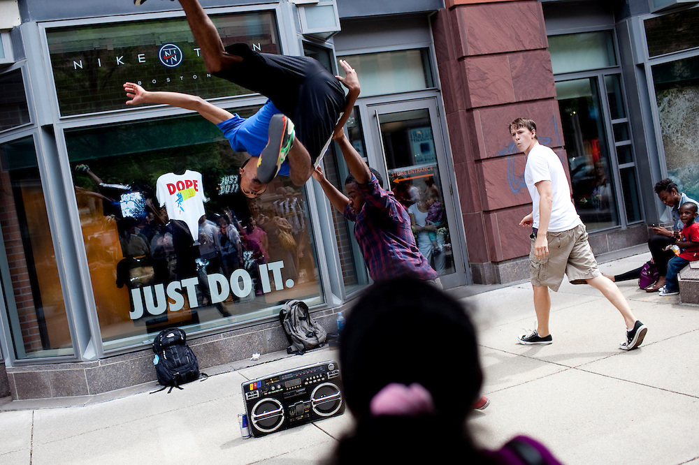 "Boston, Mass. -- Cyrus Brooks, 23, of Mattapan, flips fellow ""Old School Dropouts"" dance troupe member Freddy Suero, 24, outside the NikeTown store on Newbury Street as Brooks' dance student, Aidan Dunbar, 17, of Cambridge, right, watches, on June 26, 2011."