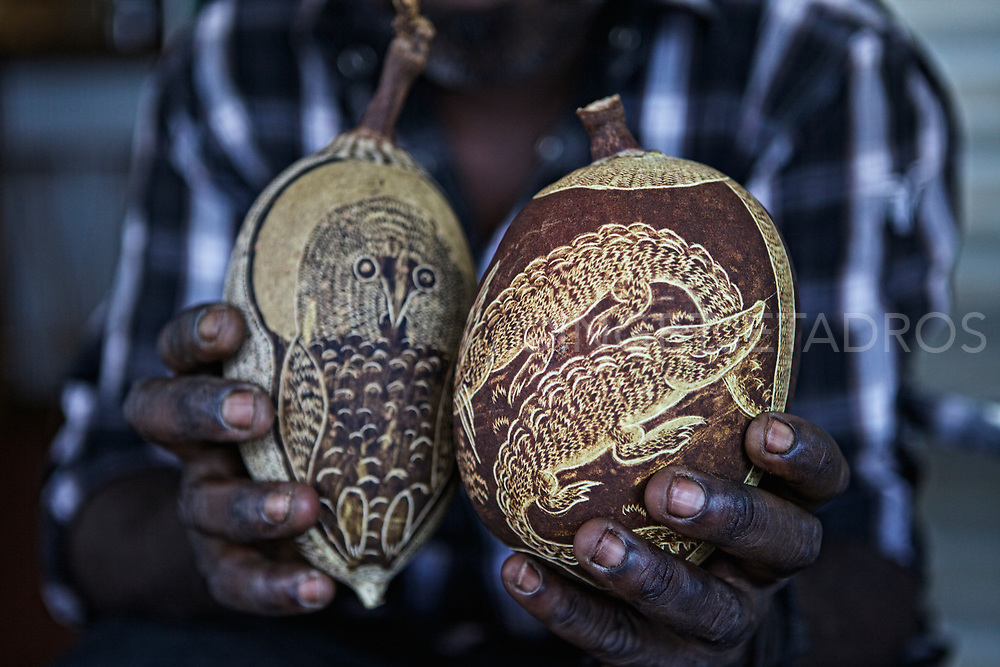 Aboriginal  carver showing his carved Boab nuts which are sold on the streets and shops in Broome. When the dark surface of the boab nut is scratched away it reveals a light colour underneath.<br /> Large and regular shaped nuts are more popular but the smaller nuts are used, too. What is most important is the time of harvest. The nut has to dry on the tree, but needs to be picked rather than fall on the ground where it will most likely crack.<br /> Motives include highly detailed faces, usually the much lined faces of Aboriginal elders, and native animals like snakes, kangaroos, birds and others, set in local landscapes. Individual artists have individual styles, the preferred motives and the preferred nut shape vary. The colour, size and hardness of the nuts depends on the location of the tree... A carved boab nut is intimately connected to the region where both the artist and the tree grew up. Broome, WA